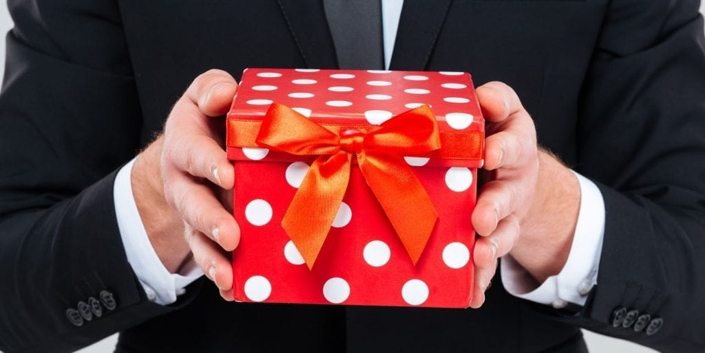 business-man-in-black-suit-holding-gift